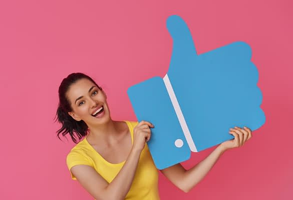 Woman holding Facebook 'tumbs up' icon